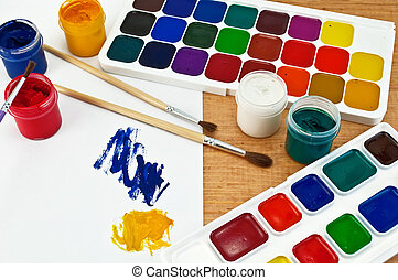 Two boxes of paint, three brushes, jars with gouache, a sheet of paper with a picture on a wooden board