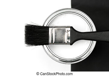 White paint and brush against black and white.