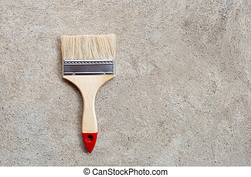 Paint brush on cement floor background.