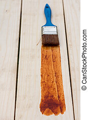 Paint brush on the painted wooden plunks board