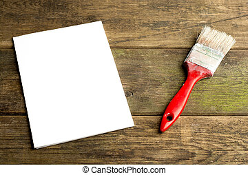 paint brush  on wooden background with empty paper