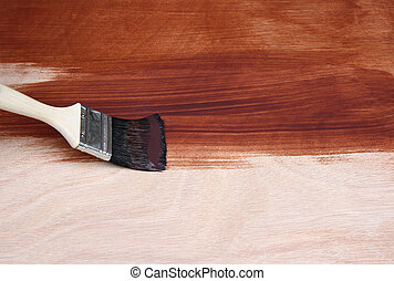 Paint brush painting a wooden surface