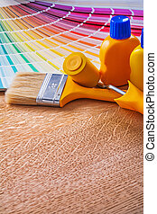 Paint brush roller and bottles with pantone fan on wooden board