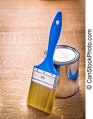 paint brush with blue handle standing near can on wooden board