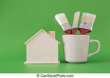 Paint brush with wooden house symbol on wooden floor background
