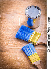 paint brushes and can on wooden board