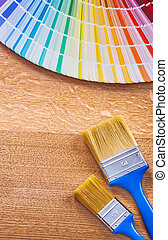 Paint brushes and pantone fan on wooden board construction conce