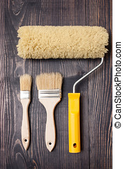 Paint brushes and roller on old wooden background