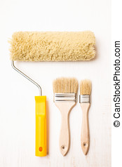 Paint brushes and roller on white wooden background