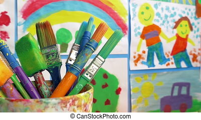 Paint Brushes In Classroom With Paintings On Wall
