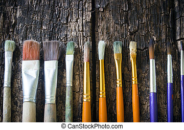 Paint brushes of different sizes have different colors in a...