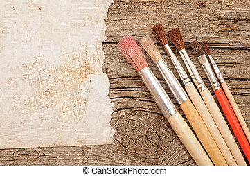Paint brushes on old wooden background with blank vintage paper