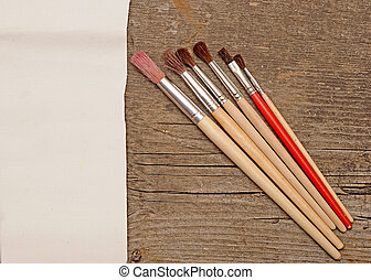Paint brushes on old wooden background with white canvas