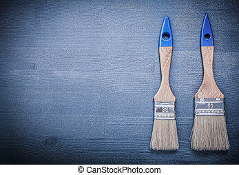 Paint brushes on wooden board construction concept