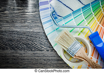 Paint brushes roller color sampler adhesive tape on wooden board