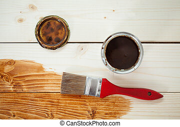 Paint can and paintbrush on wooden planks