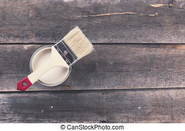 paint can with paintbrush on old wooden background