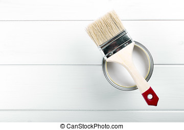 paint can with paintbrush on white wooden background with copyspace