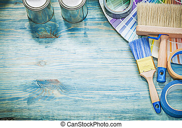 Paint cans brushes pantone fan adhesive tape on wooden board