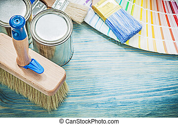 Paint cans brushes pantone fan on wooden board construction conc