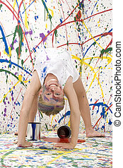 Paint Girl - Ten year old girl doing back bend towards...