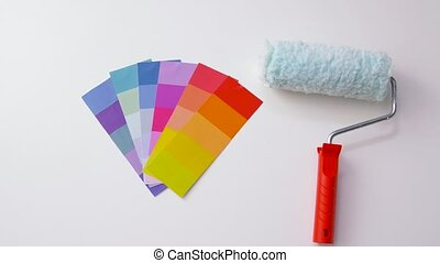 paint roller and color palette on white background