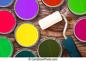 Paint roller and color tin cans of color on wooden...
