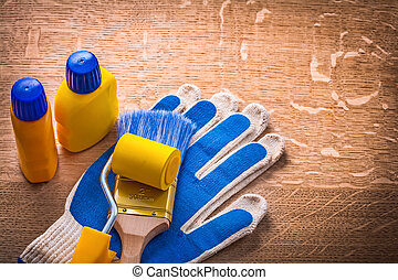 Paint roller bottles brush with protective gloves on wooden boar