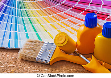 Paint roller brush and bottles with pantone fan on wooden board
