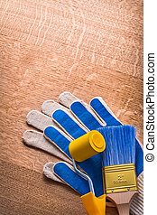 Paint roller brush with protective gloves on wooden board mainte