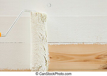 Paint roller brush with white paint on wooden background