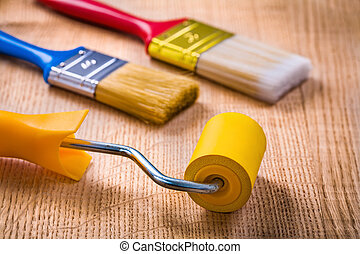 paint roller brushes on wooden board