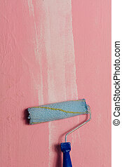Paint roller leaning against a pink wall, with a white...