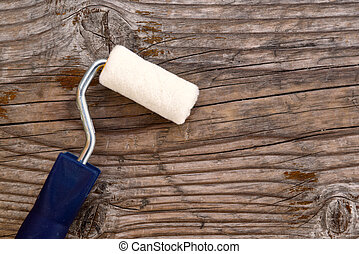 Paint roller on wooden background