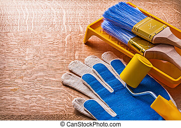 Paint roller tray brushes and protective gloves on wooden board