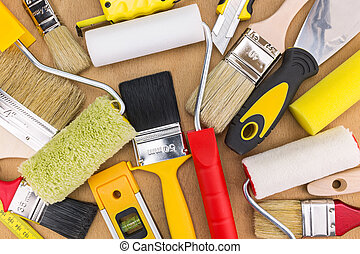 Set paint rollers and brushes on wooden background
