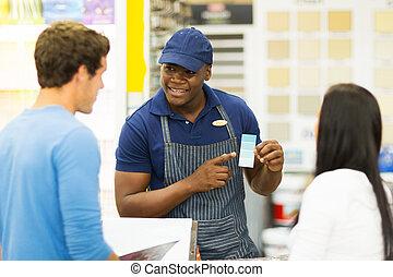 paint store salesman helping couple choosing paint color