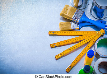 Paint tools with duct tapes and wooden meter on metallic...