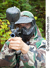 paintball player aiming looks in the face in forest