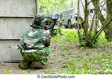 Paintball player in camouflage and protective mask hides ...