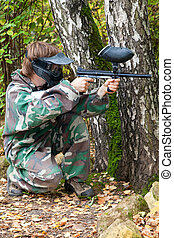 paintball player is hiding and shooting aside in the forest