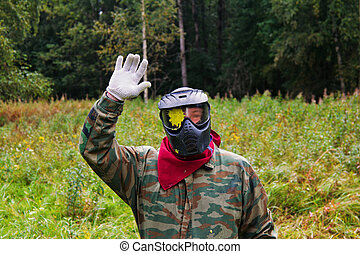 Paintball player with a spot of paint on goggles waving hand...