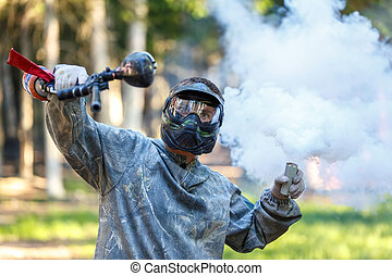 Paintball player with marker and activated smoke grenade