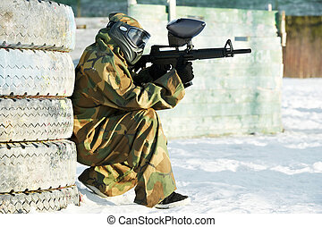 paintball player with marker at winter outdoors