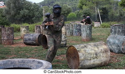 Paintball players of one team in camouflages and masks aiming with guns in shootout outdoors
