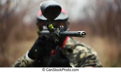 Paintball sport player aiming gun - Paintball sport player...