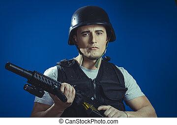 paintball sport player wearing protective helmet aiming pistol ,black armor and machine gun