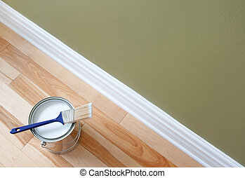Newly opened can of white paint and paintbrush on wooden floor.