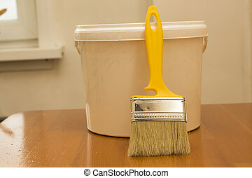 paintbrush and bucket with paint