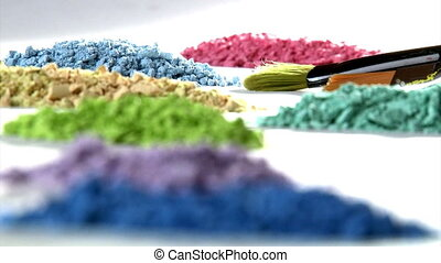 Paintbrush mixing paint. Art studio shot. Closeup. Colorful...